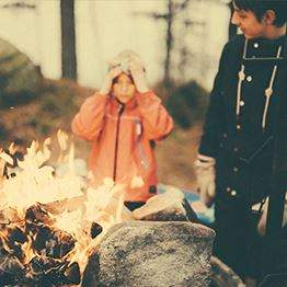 Two children wearing winter coats and hats stand around a bonfire