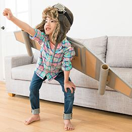 Young girl wearing cardboard rocket wings strikes a pose in her living room